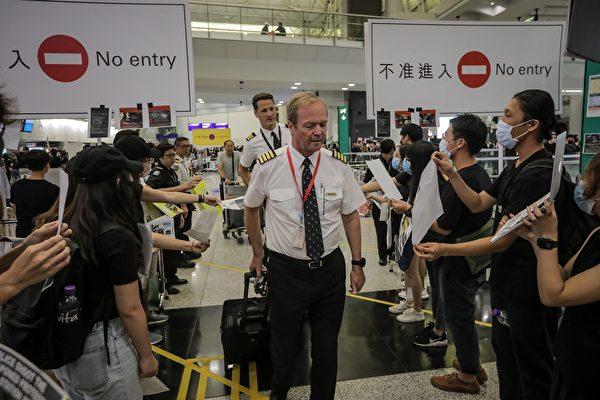 港人向最後到達的飛機機組人員致敬,並遞上「反送中」傳單。(VIVEK PRAKASH/AFP/Getty Images)