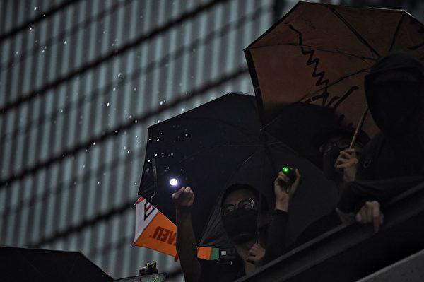 2019年8月18日晚上,遊行人士經過政府總部時,向西翼內停泊的警察車輛報以噓聲和喊口號抗議,又用雷射筆照向警員。(LILLIAN SUWANRUMPHA/AFP/Getty Images)