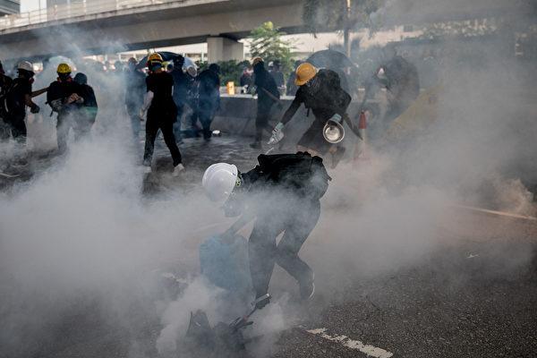 2019年8月24日,伟业街警方狂射催泪弹。游行人士用水或小铝锅浇灭、盖住催泪弹。(Chris McGrath/Getty Images)