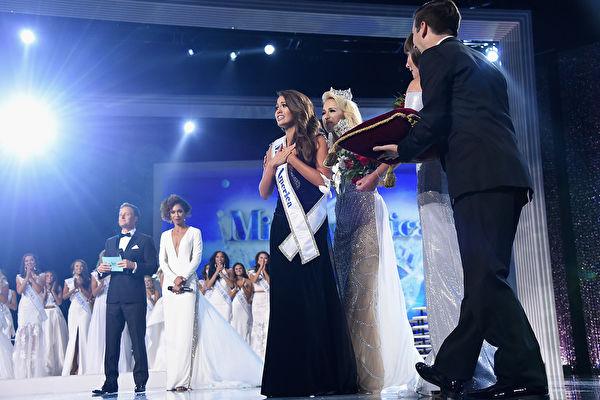 """""""2018美利坚小姐""""(Miss America)于2017年9月10日在美国新泽西州大西洋城举行最后决赛,由北达科他州小姐卡拉·蒙德(Cara Mund)摘得桂冠。她从来自全美的51名佳丽中胜出。由2017美利坚小姐席尔兹(Savvy Shields)为她戴上后冠。 (Michael Loccisano/Getty Images)"""
