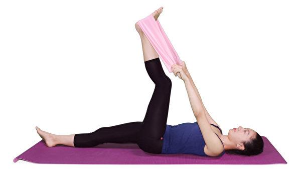 身體平躺,單腳抬起,膝蓋彎曲,用毛巾拉住腳掌提至身體上方。(攝影:李晴照)