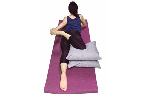 左手握住腳踝,將腳朝身體左側拉伸。