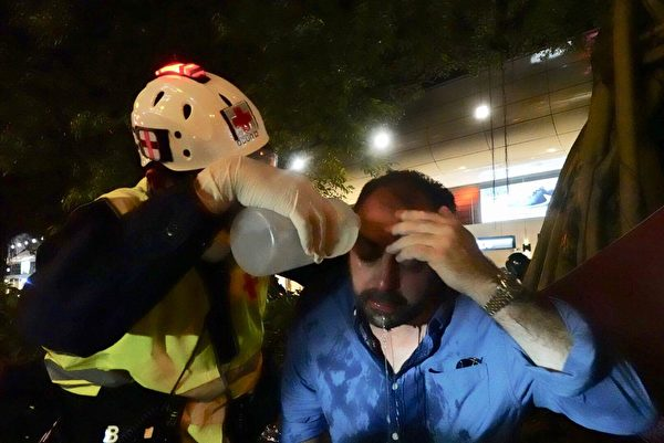 8月18日晚,尖沙嘴,警察發射催淚彈,有市民受傷,示威者幫助清洗。(余鋼/大紀元)