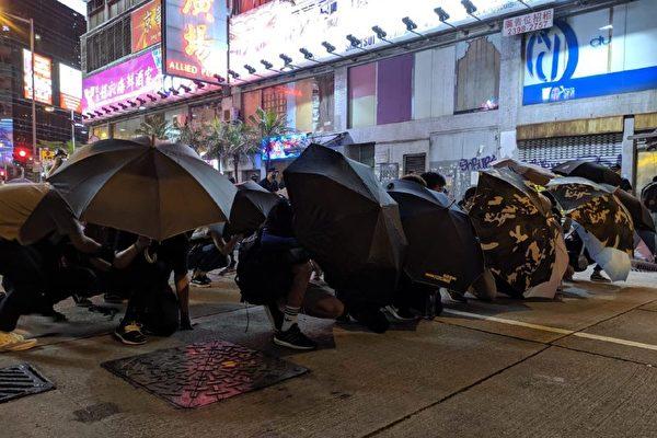 2019年9月7日晚,民众再聚太子站、旺角警署。图为民众用雨伞遮挡。(黄晓翔/大纪元)