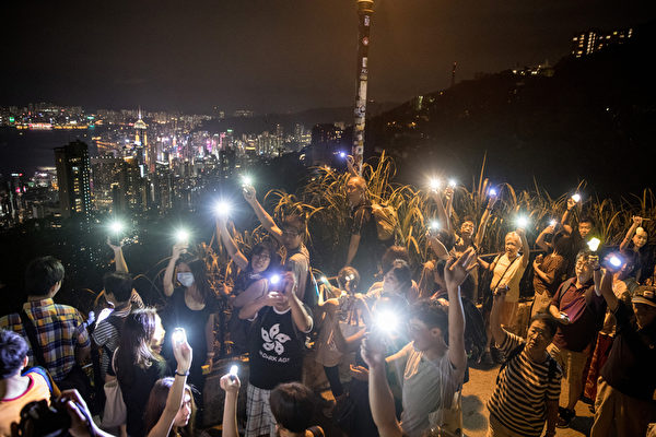 """HONG KONG, CHINA - SEPTEMBER 13: Pro-democracy protesters form a human chain and wave laser pointers, phones and lanterns in the air on Victoria Peak on September 13, 2019 in Hong Kong, China. Pro-democracy protesters have continued demonstrations across Hong Kong, calling for the city\'s Chief Executive Carrie Lam to immediately meet the rest of their demands, including an independent inquiry into police brutality, the retraction of the word """"riot"""" to describe the rallies, and genuine universal suffrage, as the territory faces a leadership crisis. (Photo by"""