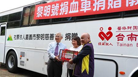 由台灣血液基金會執行長魏昇堂(左)回贈捐血車模型,由嘉義市黎明慈善會理事長施達華(右)代表接受