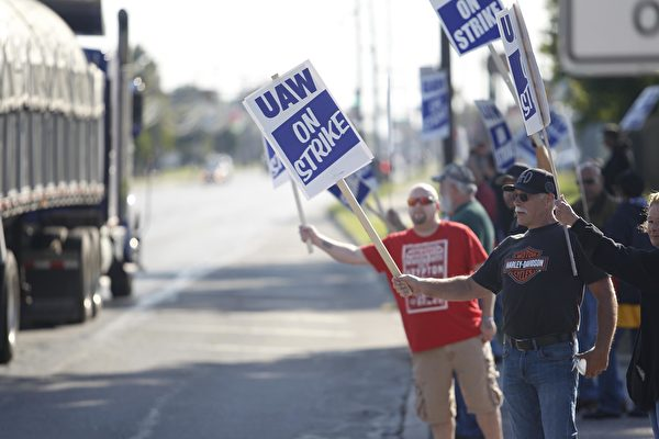 TOLEDO, OH - SEPTEMBER 18: General Motors workers wave at passing cars in front of the GM Powertrain Plant on September 18, 2019 in Toledo, Ohio. GM and the United Auto Workers union, which is leading its first strike against the auto maker since 2007, bargained into the evening yesterday and had plans to continue today over wages and health care, according to published reports citing sources familiar with the negotiations. (Photo by J.D. Pooley/Getty Images)