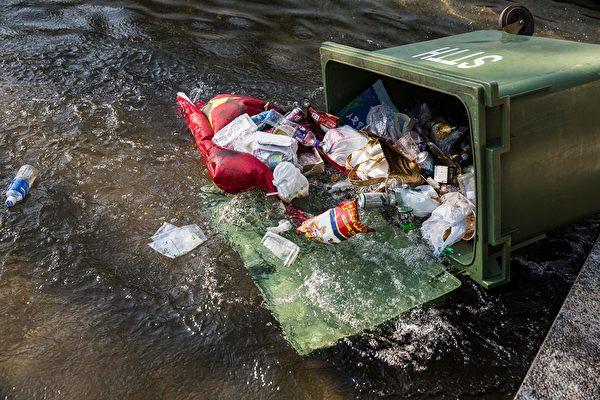 2019年9月22日,新城市聚集的民众把已经被涂污的中共五星旗扔入绿色垃圾车。(ISAAC LAWRENCE/AFP/Getty Images)
