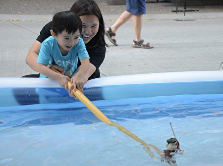 """本次文化节的主题是""""越爱台湾""""。拥有千年历史的越南水上木偶戏来到温哥华,让小朋友们亲自挥杆舞动木偶,亲子其乐融融。(余天白/大纪元)"""