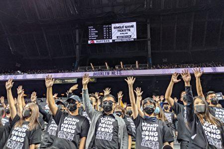 """逾150名支持香港人士坐在观众席中,穿着印有""""Stand With Hong Kong""""的黑色T恤,举起代表""""五大诉求、缺一不可""""的手势。"""