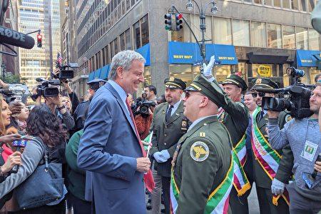 纽约市长白思豪与游行队伍指挥握手寒暄。