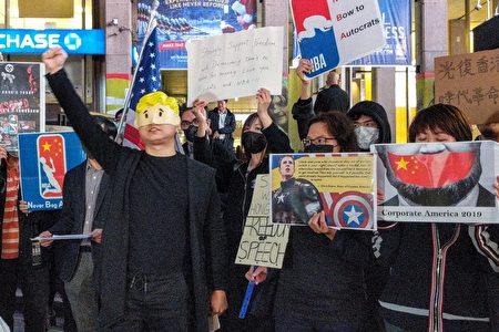 """十多位身穿黑衣的抗议者手举""""Never Bow to Autocrats""""、""""光复香港 时代革命""""等标语,呼吁NBA和美国民众继续支持香港的民主运动,并为言论自由挺身而出。"""