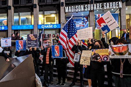 "十多位身穿黑衣的抗议者手举""Freedom of Speech""、""Stand with Hong Kong""等标语。"