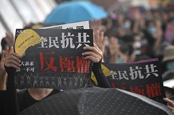 10月12日,反緊急法遊行現場,民眾舉著寫有「全民抗共 反極權」標語。(PHILIP FONG/AFP via Getty Images)