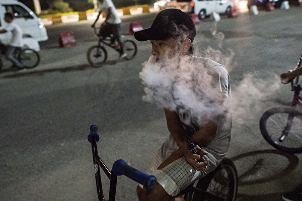 電子菸原本是幫助癮君子戒除菸癮的工具,反而引起成癮。(YE AUNG THU/AFP/Getty Images)