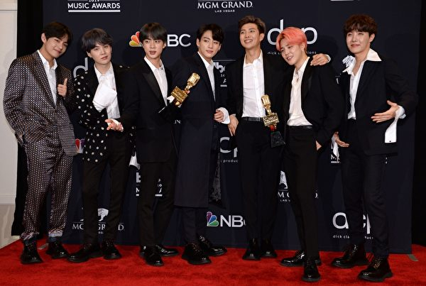 BTS poses in the press room with their awards during the 2019 Billboard Music Awards