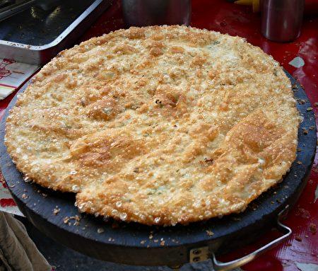 放上圓砧板上,剛起鍋、熱騰騰的低油蔥油餅。