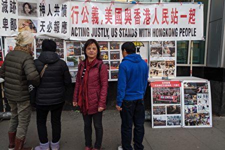 杨国英女士在法拉盛的连侬民主墙前合影留念。