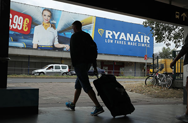 SCHOENEFELD, GERMANY - AUGUST 10: A man pulling a suitcase walks past a billboard advertisement for RyanAir during a 24-hour strike by RyanAir pilots on August 10, 2018 in Schoenefeld, Germany. RyanAir pilots in Germany, Ireland, Sweden, Belgium and Holland are taking part in the strike over demands for better pay and working conditions. (Photo by Sean Gallup/Getty Images)
