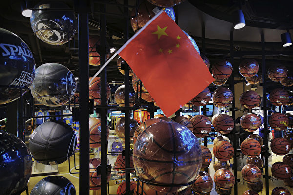 BEIJING, CHINA - OCTOBER 09: (IMAGE TAKEN WITH MOBILE PHONE CAMERA) A Chinese flag is seen placed on basketballs in the NBA flagship retail store on October 9, 2019 in Beijing, China. The NBA is trying to salvage its brand in China amid criticism of its handling of a controversial tweet that infuriated the government and has jeopardized the leagues Chinese expansion. The crisis, triggered by a Houston Rockets executives tweet that praised protests in Hong Kong, prompted the Chinese Basketball Association to suspend its partnership with the league. The backlash continued with state-owned television CCTV scrapping its plans to broadcast pre-season games in Shanghai and Shenzhen, and the cancellation of other promotional fan events. The league issued an apology, though NBA Commissioner Adam Silver angered Chinese officials further when he defended the right of players and team executives to free speech. China represents a lucrative market for the NBA, which stands to lose millions of dollars in revenue and threatens to alienate Chinese fans. Many have taken to Chinas social media platforms to express their outrage and disappointment that the NBA would question the countrys sovereignty over Hong Kong which has been mired in anti-government protests since June.(Photo by Kevin Frayer/Getty Images)