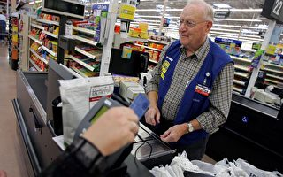 BOWLING GREEN, OH - MAY 17: Clayton Fackler, 72, works at the check out at the new 2,000 square foot Wal-Mart Supercenter store May 17, 2006 in Bowling Green, Ohio. The new store, one of three new supercenters opening today in Ohio, employs 340 people with 60 percent of those working full-time. (Photo by J.D. Pooley/Getty Images)