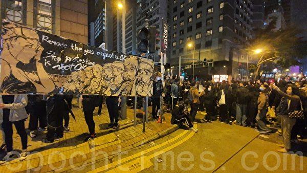 12月8日游行中,有市民举着制作的漫画表达诉求。(余钢/大纪元)
