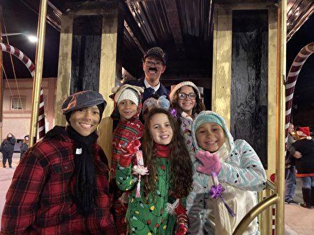 """Kelly(后者)女扮男装开着老式火车的花车,与她的孩子们拿着印有中英文""""法轮大法好""""的莲花吊坠。"""