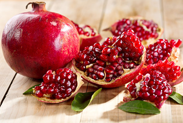 pomegranate with leafs on wooden table Fotolia