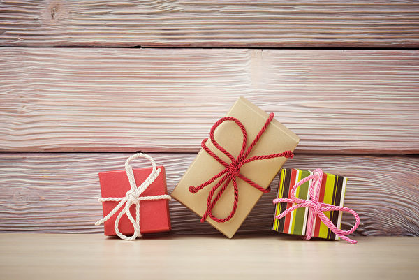 Gift boxes over light wooden background Fotolia