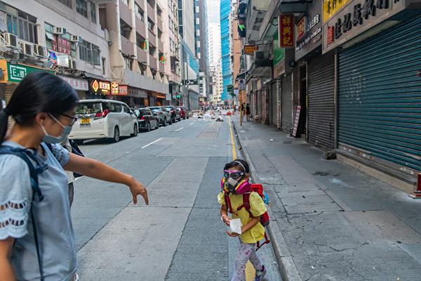 9月29日,催泪弹释放现场,妈妈招唤带着防毒面具的女儿。(Billy H.C. Kwok/Getty Images)