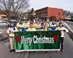 """2019年12月8日,纽约州杰维斯港(Port Jervis)举办跨州圣诞游行。法轮大法学员向道路两侧的民众祝福""""圣诞快乐""""。(戴兵/大纪元)"""