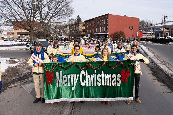 2019年12月8日,紐約州杰維斯港(Port Jervis)舉辦跨州聖誕遊行。法輪大法學員向道路兩側的民眾祝福「聖誕快樂」。(戴兵/大紀元)