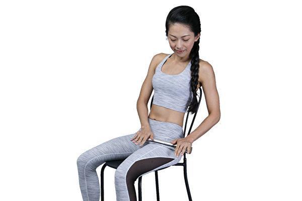 基本的筋膜放鬆操之二:雙手拿著食品用鋁箔紙芯按壓左腳大腿外側的根部。(幸福文化提供)
