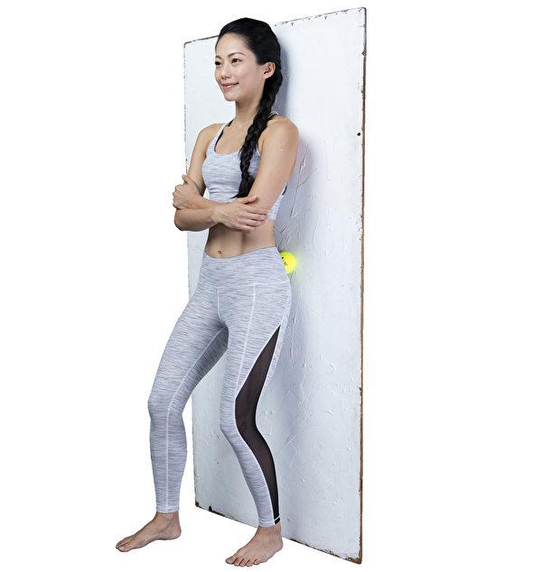 基本的筋膜放鬆操之三:用網球滾動按壓並伸展臀部外側。(幸福文化提供)
