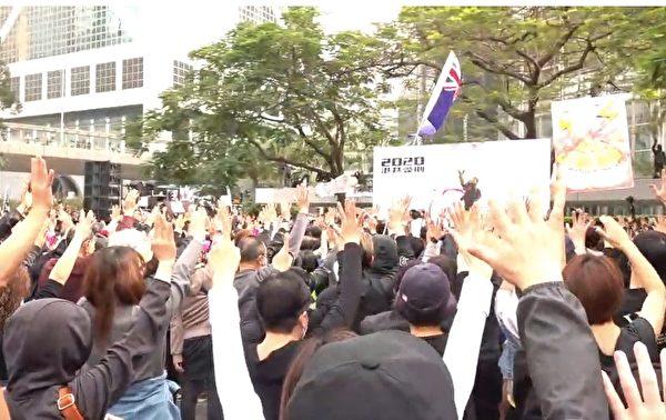 1月19日,港人举行流水式集会,现场齐唱《愿荣光归香港》,并伸出五手指,表示五大诉求。(大纪元视频截图)