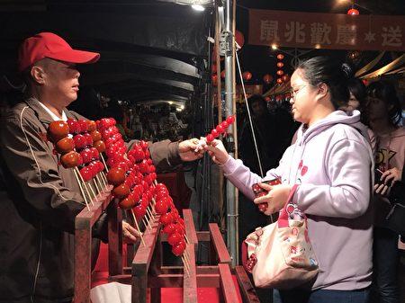 卖糖葫芦的蔡先生(左)说,每年都来年货大街摆摊,享受那年节的喜气。