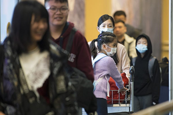 不戴着口罩的中国旅客抵达温哥华国际机场