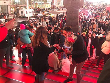 情侣选在杜菲广场(Duffy Square)求婚,男方为女友戴上钻戒。
