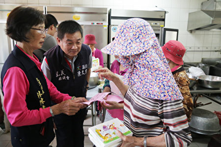 县议员陈文忠关心老长辈登记领取便当的书面资料。