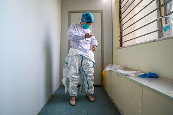 含防护衣在内的全套防护装备,单单是穿上就需要15~20分钟的时间,脱下更要小心翼翼,防止沾上病毒。(STR/Getty Images)