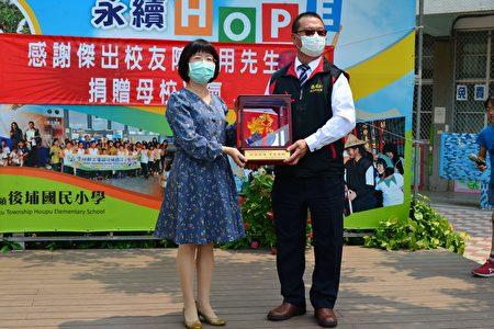 後埔國小校長黃麗鴻回贈傑出校友陳富用紀念品。感謝他對母校的回饋