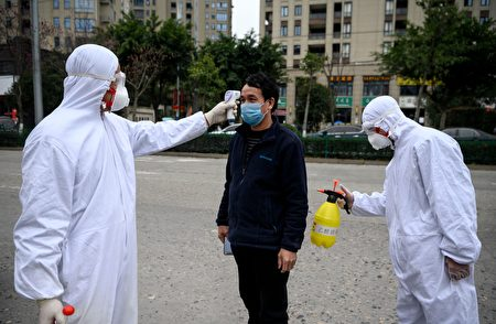 由于中共的隐匿疫情,才导致病毒的大流行。图为上班前量体温的中国劳工。