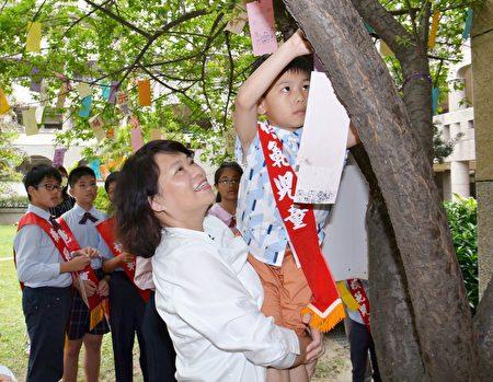 市长黄敏惠抱着大同国小模范儿童,让他将祈愿卡挂在学校的许愿树上。