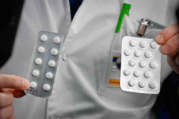 美国纽约一位医师分享他使用羟氯奎宁、日舒等药物的治疗成果。图为一位医师展示中共肺炎潜在治疗药物。(GERARD JULIEN/Getty Images)