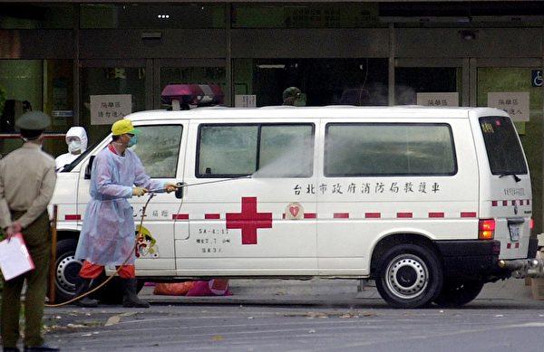 2003年4月,一名男子在台湾三军总医院松山分院门前为一辆运送SARS疑似病患的救护车消毒。(PATRICK LIN/Getty Images)