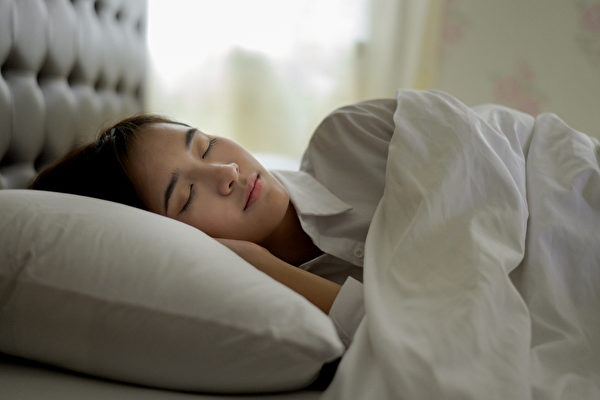 睡覺時用枕頭墊起身體,可以保持舒服睡姿,並讓身體血液循環通暢。(Shutterstock)