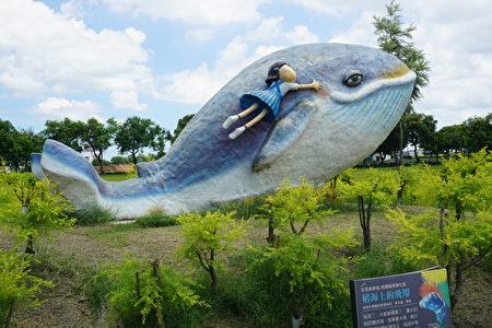 西瓜園的旁邊還有一條大鯨魚,一個小女孩乘著大魚,航行在稻浪吹拂的海洋上。
