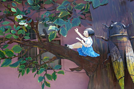 鐵雕藝術「午後的朴樹上」描述放學的午後時光,小女孩靠在大樹幹上享受悠閒的午後時光。