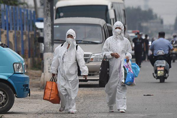 北京疫情严重,丰台区已启动战时机制;新发地由武警把守,全面封锁。图为6月13日,两女士全身穿防护服走在新发地附近街道。(GREG BAKER/AFP via Getty Images)
