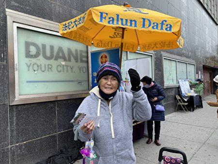 """西人民众在纽约法拉盛真相点接过""""法轮大法好""""小莲花和真相资料。"""